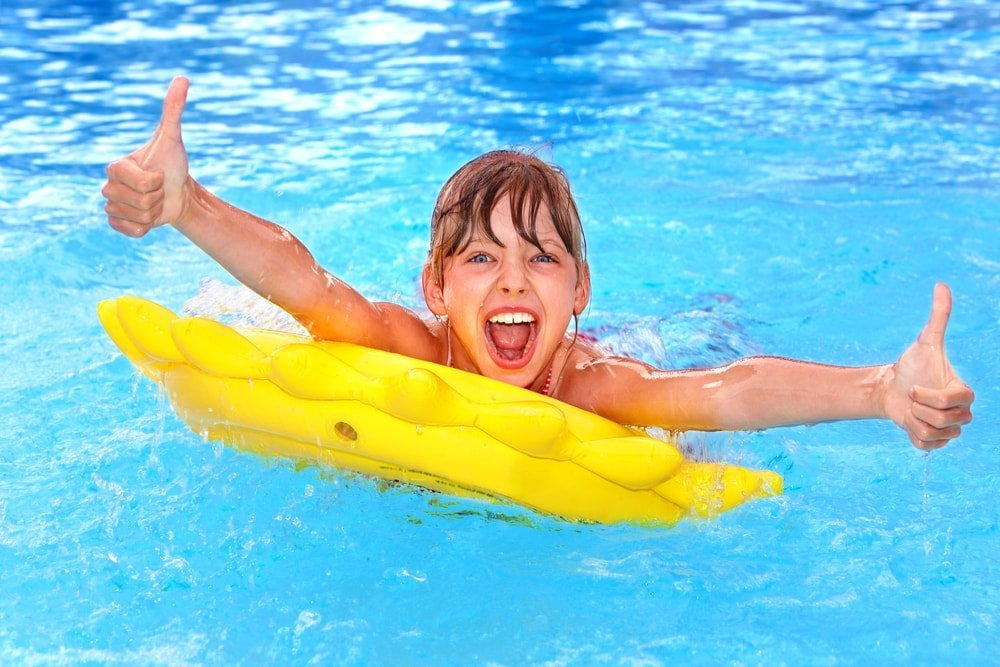 boy swimming and giving thumbs up