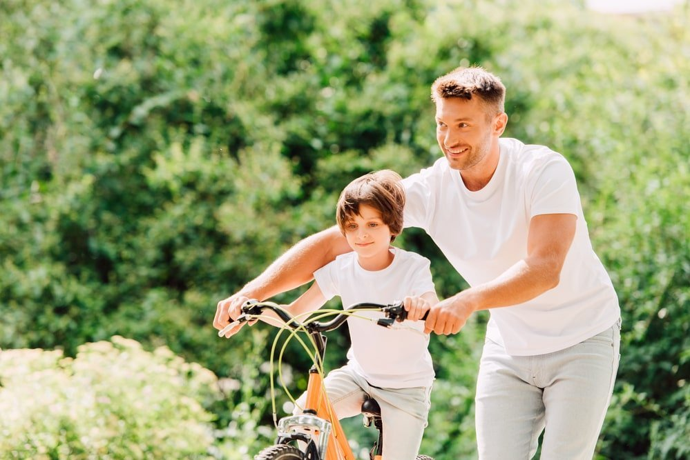 Dad Helping Son Ride A Bike For Improved Mental Health