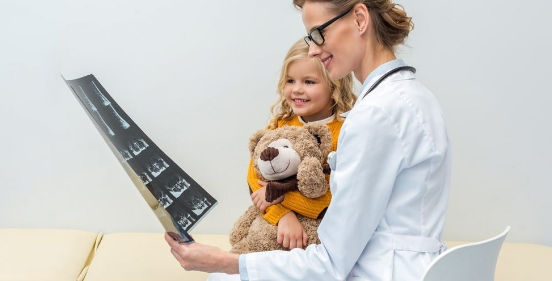 Doctor Showing X-Ray To Young Girl